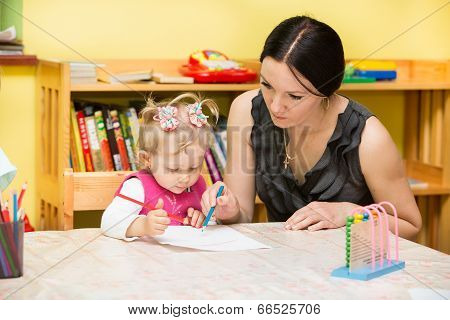 Mother And Child Girl Playing In Kindergarten In Montessori Preschool Class.