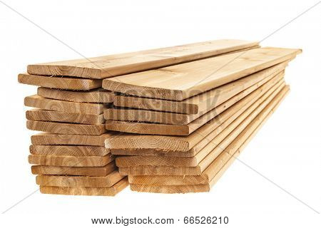 Stacks of cedar one by six inch wood planks on white background