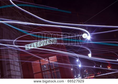 London telephone box and Big Ben in background at night. With light trails.