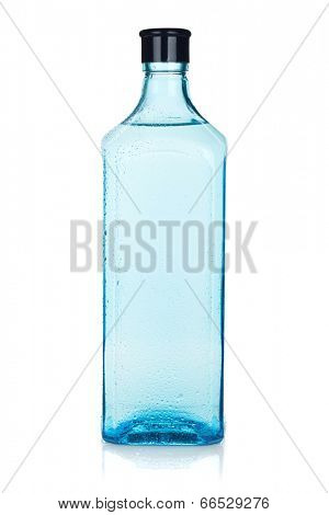 Glass gin bottle with water drops. Isolated on white background