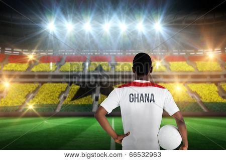 Ghana football player holding ball against stadium full of ghana football fans