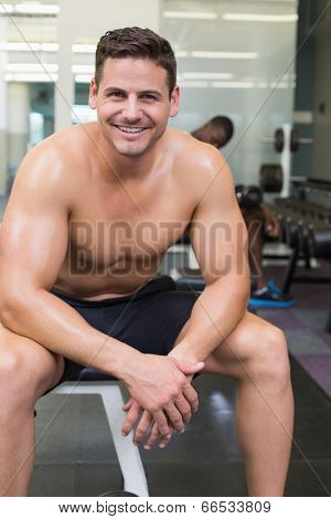 Handsome smiling bodybuilder sitting on bench in weights room at the gym