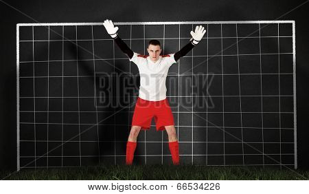 Composite image of goalkeeper in red and white ready to catch against goal net