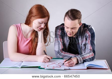 Teenage Couple Drawing Hearts Instead Of Learning