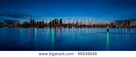 Toronto skyline panorama at dusk over lake with colorful lights