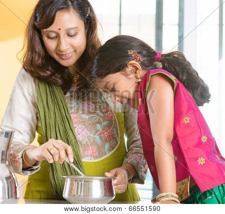 Asian family cooking food together at home. Indian mother and child preparing meal in kitchen. Traditional India people with sari clothing.