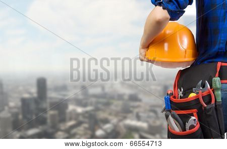 Close up of woman mechanic with yellow helmet in hand against city background