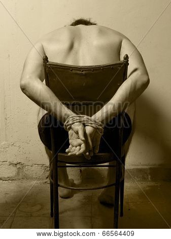 Tortured Man In A Chair With Tied Hands. Sepia Tone