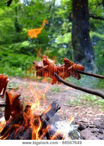 Roast sausages over a fire.