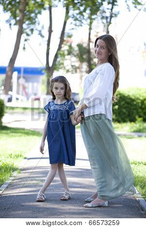 Portrait in full growth, mother and eight year old daughter in a summer park