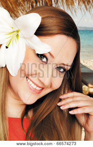 Portrait of a young smiling woman with lilly in hair on beach vacation. Work path.