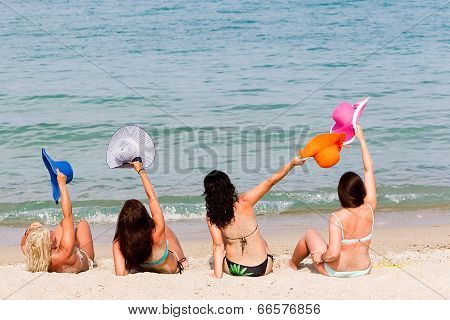 Back View Of Four Young Playful Women In Summer Hats Resting On The Beach And Enjoy The Tropical Sea