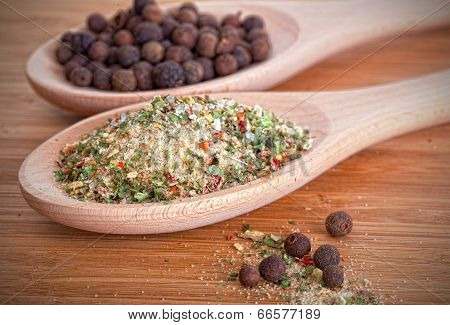 Salt with herbs and allspice in wooden spoons