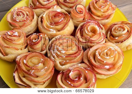 Tasty  puff pastry with apple shaped roses on plate on table close-up