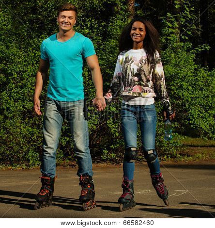 Multi ethnic teenage couple on a rollerblades in a park
