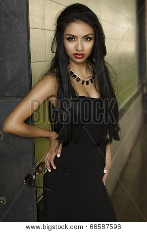 Beautiful exotic young woman wearing black dress