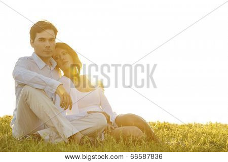 Portrait of confident young man sitting with girlfriend on grass against clear sky