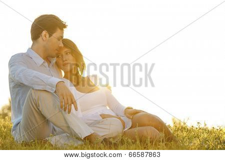 Loving young couple sitting on grass against clear sky