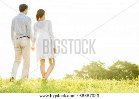 Rear view of young couple holding hands in park against clear sky