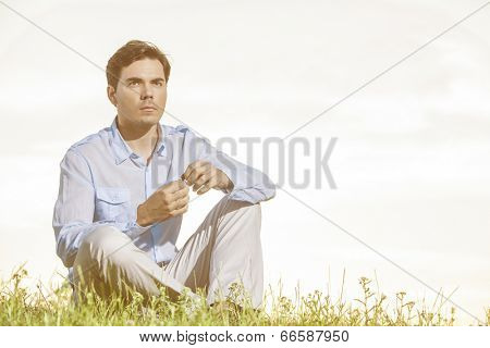 Thoughtful young man looking away while sitting on grass against clear sky