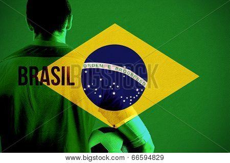 Brasil football player holding ball against brasil national flag