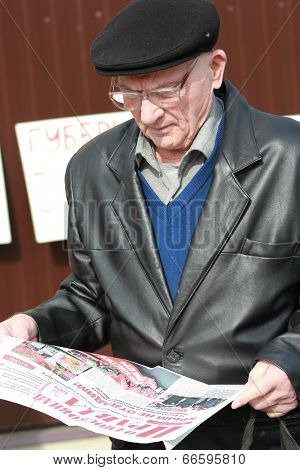 The unknown old man reads propaganda newspaper on the opposition rally.