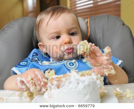 Little boy eating first birthday cake