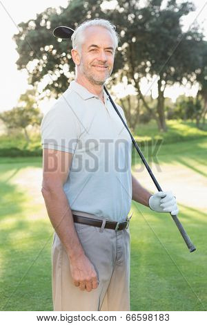 Smiling handsome golfer looking at camera on a sunny day at the golf course