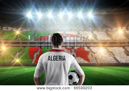 Algeria football player holding ball against stadium full of algeria football fans