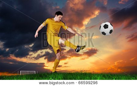Football player in yellow kicking against green grass under blue sky