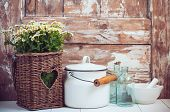 picture of wooden basket  - Flowers in a wicker basket glass bottles and vintage milk can on wooden background cozy home rustic decor cottage living