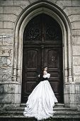stock photo of victorian houses  - Mysterious woman in Victorian dress with old doors - JPG