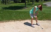 foto of ladies golf  - Woman prepares to swing at the golf ball caught in the sand bunker - JPG