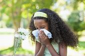 stock photo of hay fever  - Young girl sitting by flower and blowing her nose in the park on a sunny day - JPG