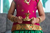 image of deepavali  - Diwali or deepavali photo with little girl hands holding oil lamp during festival of light - JPG