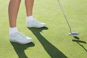 stock photo of ladies golf  - Lady golfer on the putting green on a sunny day at the golf course - JPG
