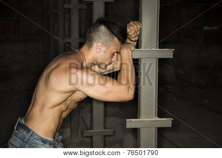 Muscular Shirtless Young Man Resting Against Metal Column
