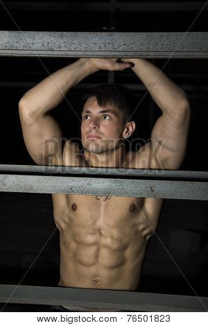 Muscular Shirtless Young Man Resting Against Metal Structure
