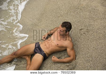 Attractive Shirtless Muscleman In Swimming Suit Lying On The Beach