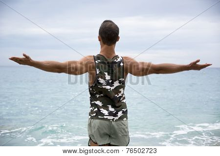 Muscular Young Man On The Beach Seen From The Back