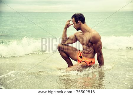 Handsome Muscular Young Man On The Beach Sitting In The Sea