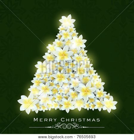 Beautiful X-mas tree decorated with flowers on shiny green background for Merry Christmas celebrations.