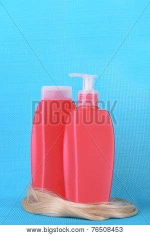 Shampoo and hair conditioner with curly blond hair on blue background