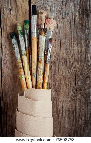 Artist Paintbrushes And Roll Of Canvas On Wooden Background