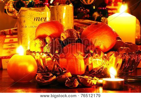 Fruit with candles and Christmas presents.