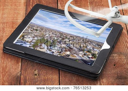 cityscape of Fort Collins, Colorado - reviewing aerial pictures from a low flying drone on a digital tablet with spinning drone rotor in background, screen image created by the photographer
