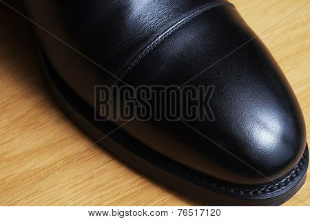 Front detail of a black leather classic shoe on a dance floor