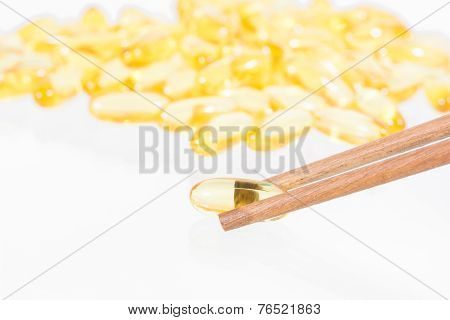 Omega 3 Fish Oil Capsules On Wooden Chopsticks
