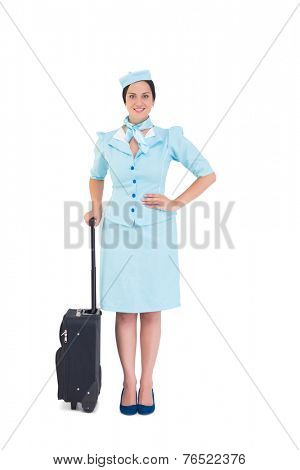 Pretty air hostess holding suitcase on white background