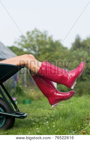 Woman in welly boots in wheelbarrow at home in the garden